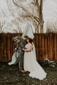 Groom in blue suit and bride in blush dress stand kiss at ceremony