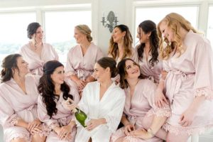 Bridesmaids get ready in pink robes with bride in white robe