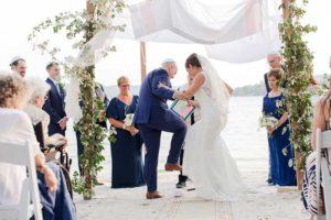Bride groom break glass at lake wedding