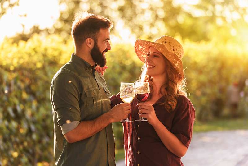 Man green shirt woman red shirt cheers at winery
