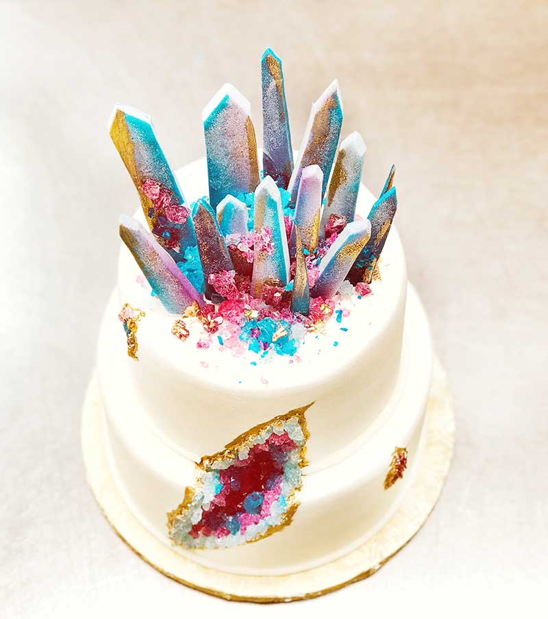 White wedding cake with rainbow geode and crystals