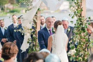 Bride in white dress and groom in blue suit during ceremony