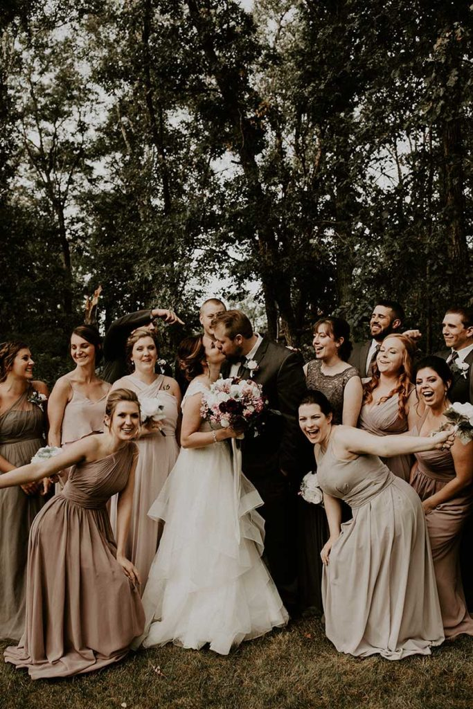 Wedding party in mauve and tan dresses celebrate wedding