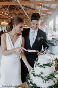 Bride white dress groom navy suit cut wedding cake