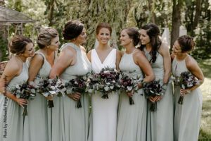 Bride in modest white dress stands with bridesmaids in sage green dresses
