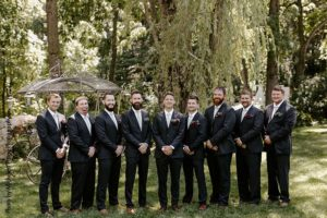 Groomsmen and groom in navy suits stand outside