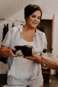 Bridesmaid pours champagne