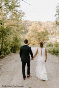 Bride and groom walk on dirt road
