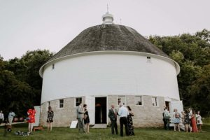 Wedding guests stand outside Round Barn Farm