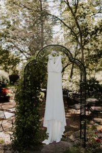 White bridal dress hangs on black arch outside